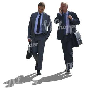 two backlit businessmen walking side by side