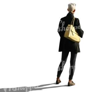 backlit woman with a yellow purse standing