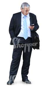 cut out elderly businessman standing and looking at his phone