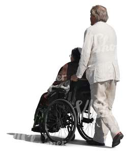 elderly man pushing a woman in a wheelchair