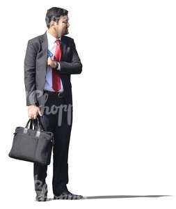 indian businessman in a suit standing with a bag in his hand