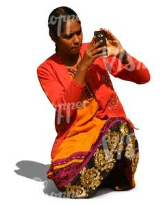indian woman kneeling and taking a picture