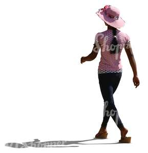 backlit black woman wearing a pink hat walking