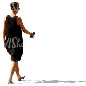 woman in a black summer dress walking barefoot on the beach