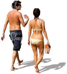 man and woman walking barefoot on the beach and talking