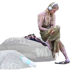 woman sitting on a rock and listening to music