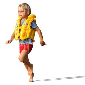 boy in a swim vest running on the beach