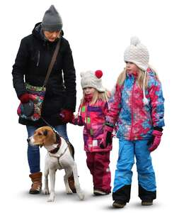 family with two children and a dog walking in wintertime