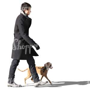 asian man in a black coat walking a dog