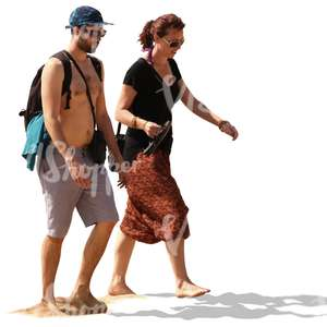 couple walking barefoot on a sandy beach