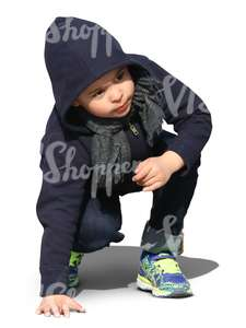 little boy squatting and looking up