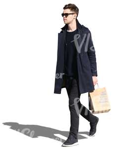 man wearing a black jacket walking with a shopping bag