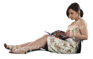 woman sitting on a couch and reading a magazine