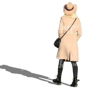 woman wearing a beige coat and hat walking