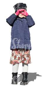 little girl wearing a winter jacket standing in the sunlight