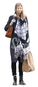 woman with a big scarf and a shopping bag standing