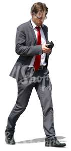 businessman walking and looking at his phone