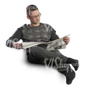 man sitting on a sofa and reading newspaper