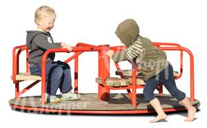 two boys playing on a carousel