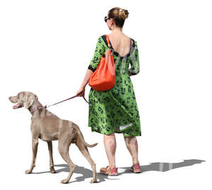 woman in a green dress walking a dog