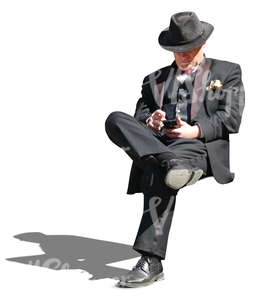 man in a black formal suit sitting and looking at his phone