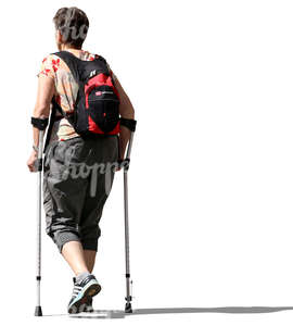 older woman walking with crutches