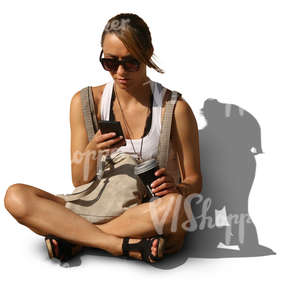woman sitting on the ground and looking at her smartphone