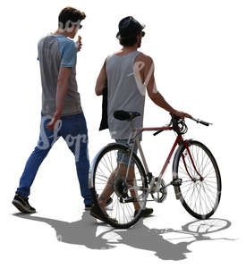 two backlit men walking and one has a bike