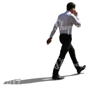 backlit businessman walking and talking on the phone