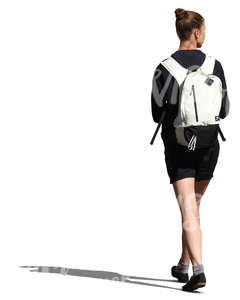 woman with a white backpack walking in the sunlight