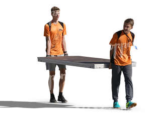 two teenage boys carrying a large table