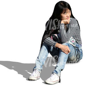 asian woman sitting on the sidewalk