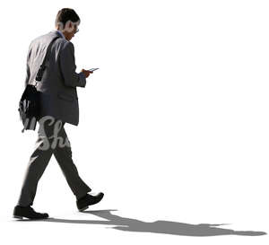backlit businessman walking while looking at his phone