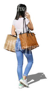 woman with shopping bags walking and talking on the phone