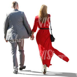 backlit couple in formal outfits walking hand in hand