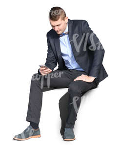 young man wearing a suit sitting and browsing his phone