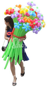 woman in a blue dress walking and carrying balloon flowers