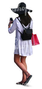 woman with a large hat and white dress doing some shopping