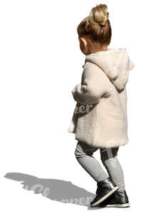 small girl with a beige cardigan walking on the street