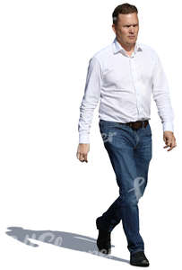 man in a white shirt and jeans walking in sunlight