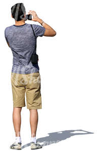 man in shorts standing and taking a picture