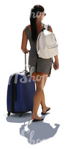 backlit woman in a summer dress walking with a big suitcase