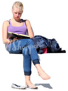 teenage girl sitting outside and reading a book
