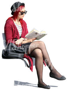 woman with sunglasses sitting outside and reading