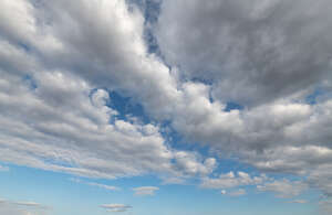 pale blue daytime sky with large white clouds