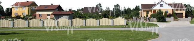 suburbian area with houses and a fence
