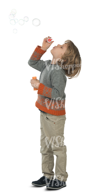 young boy standing and blowing bubbles