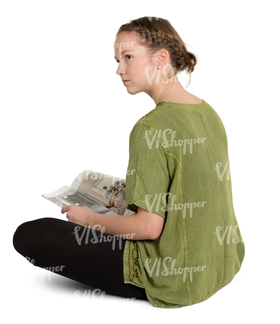 teenage girl sitting on a floor and reading a magazine