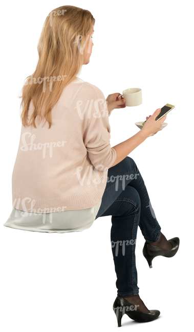 woman sitting and drinking coffee and looking at her phone