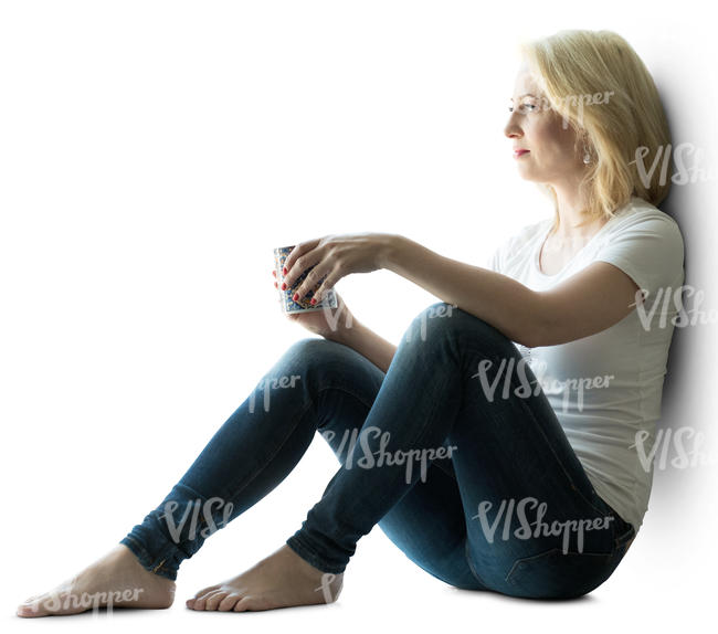 backlit woman sitting by the window and drinking coffee